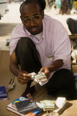 A money changer counts a wad of notes at his stall in Hargeisa market.
