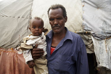 A man and his child stand together outside a makeshift tent in  Dami IDP (internally displaced people) camp.