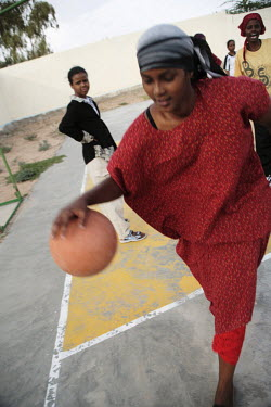 A young woman plays basketball at Socsa (Somaliland Culture and Sports Association).