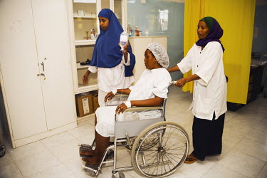 A pregnant woman is wheeled, by female medical staff, into an operating theatre in Edna Adan Hospital.