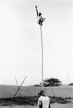 A boy training in the Hargeisa circus balances atop of a pole supported on the chin of another performer.
