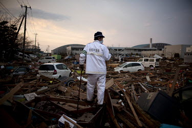 A rescue worker searches for bodies amongst the debris at Sendai airport. On 11 March 2011 a magnitude 9 earthquake struck 130 km off the coast of Northern Japan causing a massive Tsunami that swept a...