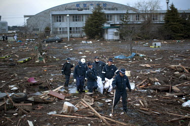 A rescue team carry a body they uncovered from the debris at Sendai airport. On 11 March 2011 a magnitude 9 earthquake struck 130 km off the coast of Northern Japan causing a massive Tsunami that swep...