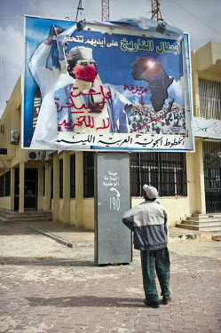 A man stares up at a defaced poster of A carpet woven with the picture of Col. Muammar Gaddafi on a Benghazu street. On 17 February 2011 Libya saw the beginnings of a revolution against the 41 year re...