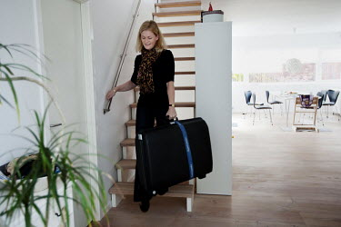 Cecilie carries her suitcase as she prepeares to go to Kathmandu, at her home in Gentofte. 19 month old Victoria (formerly named Ghane) was born with hydrocephalus and was left abandoned. Cecilie Hans...