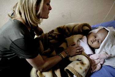 Cecilie tucks in Victoria as she prepares to leave the Annapurna Neurological Institute in Kathmandu. 19 month old Victoria (formerly named Ghane) was born with hydrocephalus and was left abandoned. C...