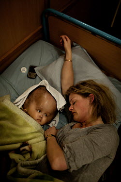 Cecilie sleeps next to Victoria at Annapurna Neurological Institute in Kathmandu. 19 month old Victoria (formerly named Ghane) was born with hydrocephalus and was left abandoned. Cecilie Hansen was so...
