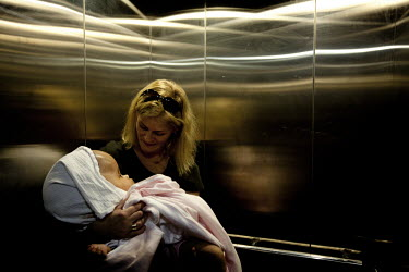 Cecilie holds Victoria in a lift at the Annapurna Neurological Institute in Kathmandu. 19 month old Victoria (formerly named Ghane) was born with hydrocephalus and was left abandoned. Cecilie Hansen w...