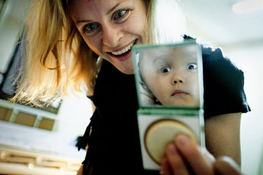 Cecilie shows's Victoria what she looks like in a mirror at the Annapurna Neurological Institute in Kathmandu. 19 month old Victoria (formerly named Ghane) was born with hydrocephalus and was left aba...