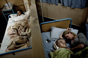 Cecilie sleeps next to Victoria at Annapurna Neurological Institute in Kathmandu while another patient sleeps next door. 19 month old Victoria (formerly named Ghane) was born with hydrocephalus and wa...
