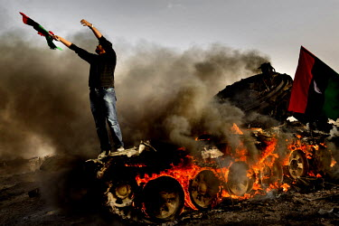 A man waving a pre-Gadaffi era Libyan flag stands on a burning tank that had been a part of the pro-Gadaffi forces attacking Ajdabiya. On 17 February 2011, an uprising against the 41 year rule of Col....