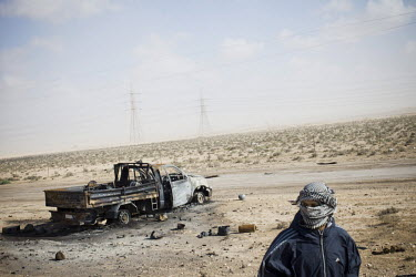 A young rebel fighter stands near a burnt out car at the front line between Ajdabiya and Brega. On 17 February 2011 Libya saw the beginnings of a revolution against the 41 year regime of Col Muammar G...