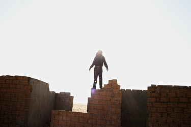 A rebel fighter stands on a wall near the front line outside Ajdabiya. On 17 February 2011 Libya saw the beginnings of a revolution against the 41 year regime of Col Muammar Gaddafi.