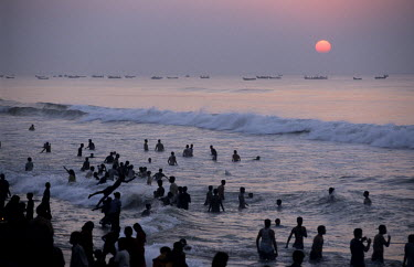 Devotees taking a ritual bath at sunrise on the first day of the Hindu month of Kartika which begins with the new moon.
