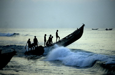 A motorised fishing boat rides the surf as it heads out to sea.