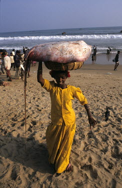 A woman carries a ray in a basket on her head away from a beachside market.