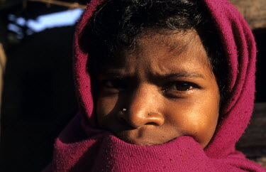 A Desia Kondh tribal girl wrapped up against a cold morning.