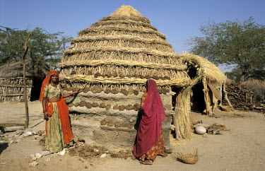 Two women building a mud and straw hut.