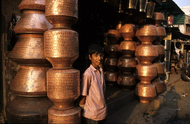 A boy stands next to stacks of copper vessels being sold in Gandi Square.