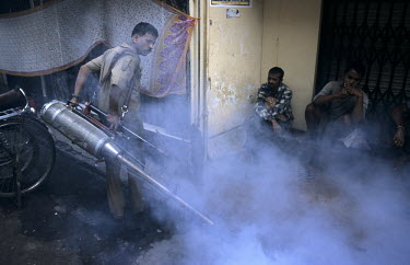 A man fumigates the streets in the Kalbadevi District.
