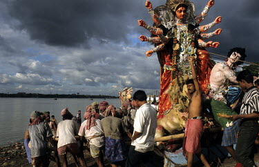A statue of the Goddess Durga is immersed into the Hooghly River during a festival in the Goddess Durga's honour.