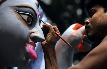 A clay statue of the Goddess Kali is painted by a man in the KumarTuli potter's district.