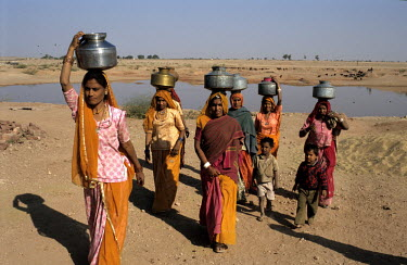 Women and children return from a trip collecting water from a lake near the village of Khichan.