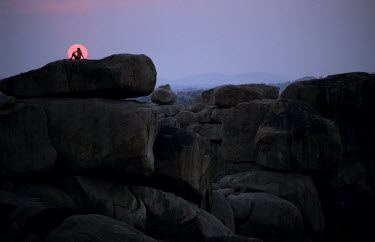 A tourist sits on a boulder, on Hemakutam Hill, sihouetted against the setting sun.