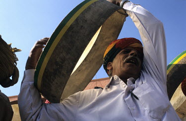 A man plays a drum during a camel festival.