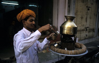 A vendor of Masala tea pours a cup of tea.