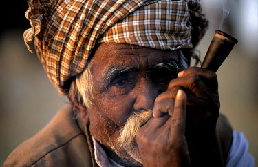An elderly man smokes tobacco in a chillum.