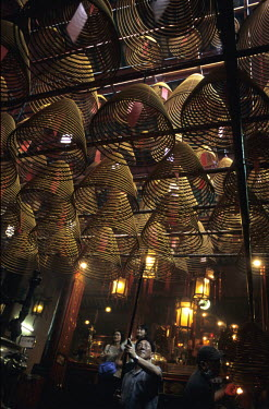 A temple employee hangs large coils of burning incense onto a rack suspended from the ceiling at the Hollywood Road Man-Mo Temple. Built between 1847 and 1862 and dedicated to the God of Literature (M...