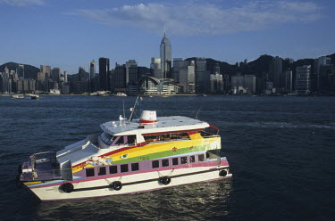 A colourful tourist boat in Kowloon Bay with the Hong Kong Island skyline beyond. The central building is the New Convention Centre.