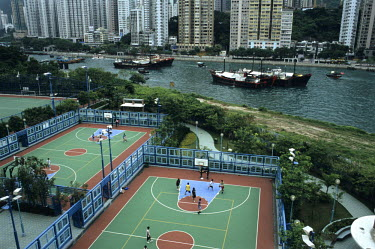 People playing basketball in some courts next to Hong Kong Harbour with highrise housing blocks beyond.