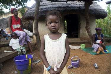 A young girl standing outside her family home.