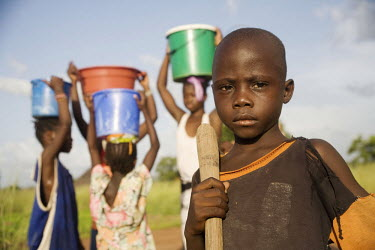 A young boy working in a field stands in front of  a group of girls standing with buckets of water that they have collected from a nearby well.
