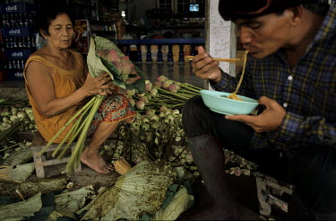 A woman prepares bunches of Lotus buds prior to sale at a Bangkok market while a man takes a break and eats a bowl of noodles.