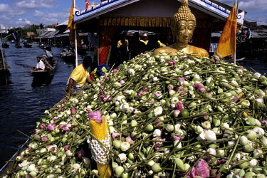 A barge carrying a Buddha statue is adorned by thousands of Lotus flowers during a Lotus festival procession along one of Bangkok's canals.
