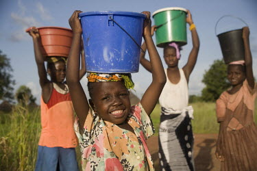 A group of girls standing with buckets of water on their heads near a well.