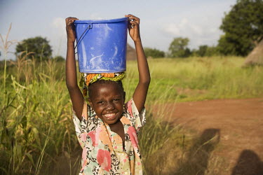 A girl standing with a bucket of water on her head near a well.