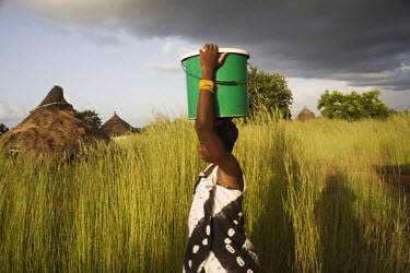 A woman carrying water in a rural village.
