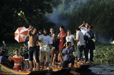 Devotees throwing Lotus buds onto a barge carrying a Buddha statue on a canal during a Lotus festival.