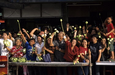 Devotees throwing Lotus buds onto a barge carrying a Buddha statue a canal during a Lotus festival.