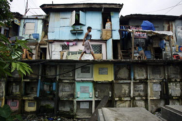 A young man walks past a house above graves in North Cemetery, home to thousands of destitute Filipinos. Most of them are the descendents of grave diggers and masons. They make a very small income fro...