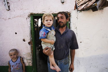 A Roma man holds his son outside a derilect building in Vranjevac.  During the NATO bombing of Kosovo in 1999, the entire Roma community of Vranjevac fled. They returned home after 2002 when their hou...