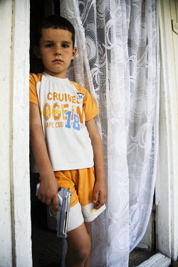 Seven year old Uros Janicievic an internally displaced (IDP) Serb, stands in a window of his home in Zubin Potok holding a toy gun. Formerly from Pristina, the family had to escape during the 1999 war...