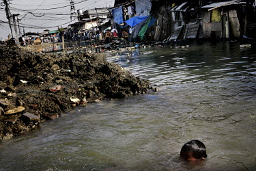 A boy swims in the shanty town of Santo Nino. People in this area live in small homemade huts, many made entirely from rubbish and leftover building materials that they found on the nearby garbage dum...