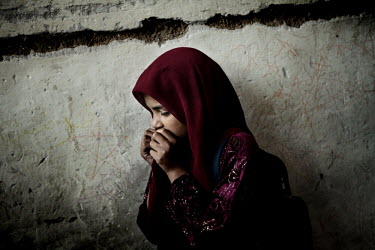 A fearful girl holds her hands to her face at the Bazar-e Gharbi girls school.