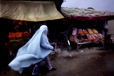 A woman's light blue burqa flutters in the wind as she walks through a rainswept market.