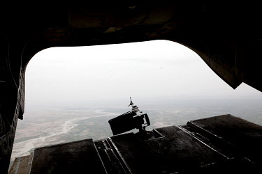 An unmaned machine gun mounted on the cargo door of a Chinook helicopter that is flying over Helmand province.